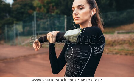 Portrait of a young fitness woman with armband stretching hands Stock photo © deandrobot