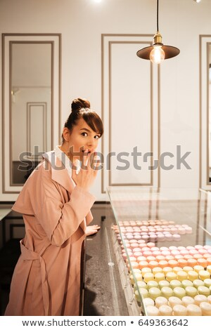Pretty young woman choosing pastry while looking through glass showcase Stock photo © deandrobot