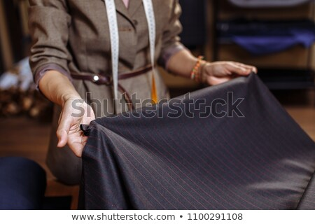 Cropped image of seamstress holding piece of fabric Stock photo © deandrobot