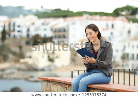 woman sitting on balcony holding hand stock photo © is2