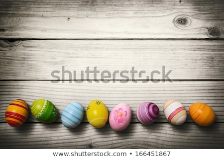 Easter nest with yellow easter eggs on a white wooden background Stock photo © Zerbor