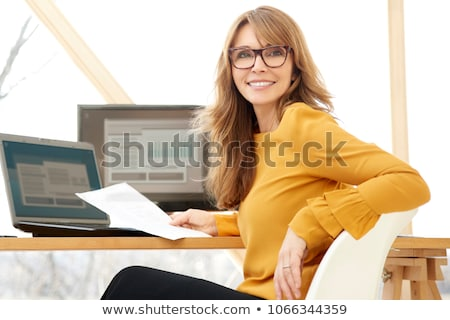 mature woman sitting at desk stock photo © is2