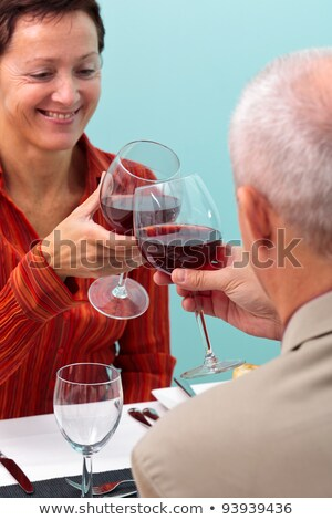 Stock photo: Couple chinking glasses with red wine