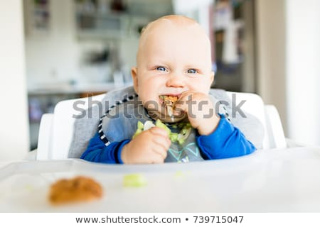 Stock photo: Baby boy eating with BLW method, baby led weaning