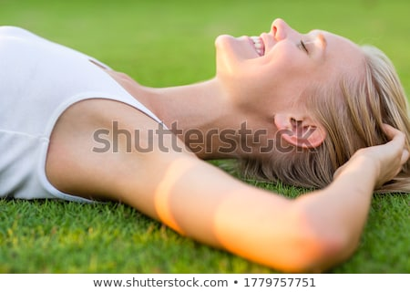Young woman lying on grass with eyes closed Stock photo © IS2