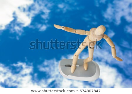 Wooden figurine standing with arms spread on a mouse Stock photo © wavebreak_media