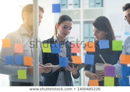 business people that work together in office with post it notes in foreground concept of teamwork a stock photo © alphaspirit