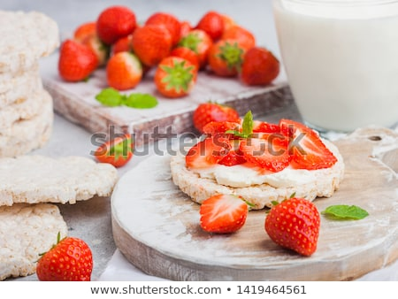 healthy organic rice cakes with ricotta and fresh strawberries on wooden board and glass of milk on stock photo © denismart