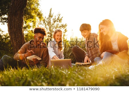 group of happy multhiethnic students doing homework stock photo © deandrobot