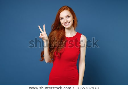 image of charming woman 20s wearing red dress laughing and stand stock photo © deandrobot