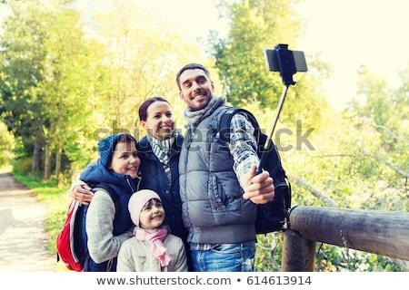 family taking photo by selfie stick outdoors Stock photo © dolgachov