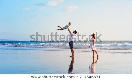 Happy family father, mother, son with fun along sunset sea surf on black stock photo © Lopolo