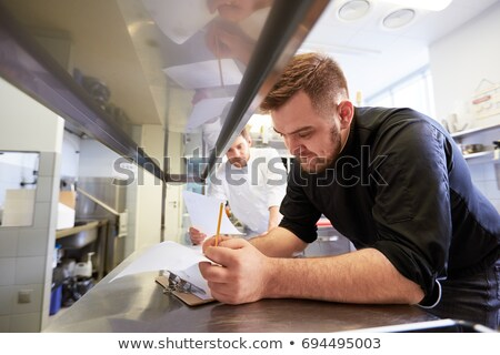 chef with clipboard doing inventory at restaurant Stock photo © dolgachov