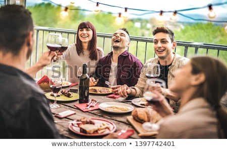 Stock photo: happy friends eating at barbecue party on rooftop