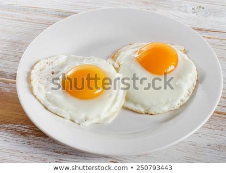 Fried eggs in plate Сток-фото © YuliyaGontar