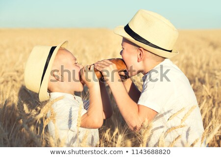 Stock photo: Two brothers eat black round bread on a wheat field.