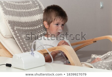 Stock photo: sick boy in nebulizer mask making inhalation, respiratory procedure by pneumonia or cough for child,