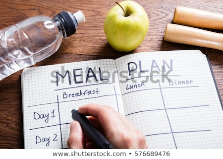 Person's Hand Filling Meal Plan On Notebook Stock photo © AndreyPopov