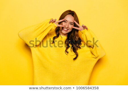 Cheerful happy curly woman in casual clothes showing peace gesture Stock photo © deandrobot