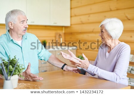 Contemporary senior spouses sitting by wooden table Stock photo © pressmaster