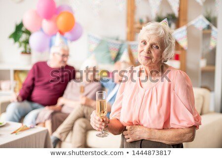 Gracious senior female with flute of champagne Stock photo © pressmaster