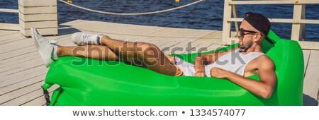 молодым человеком отдыха воздуха диван морем Сток-фото © galitskaya