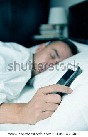 young man in bed grabbing his smartphone Stock photo © nito