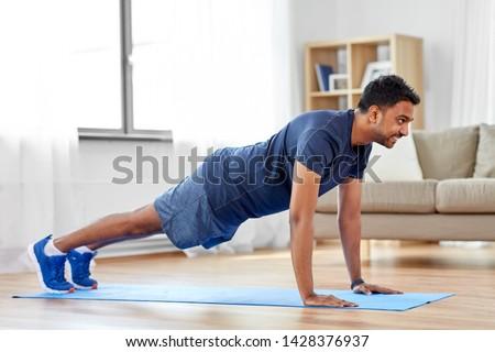 indian man doing push ups at home Stock photo © dolgachov