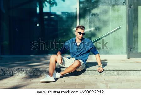 fashion man in blue shirt and sunglasses sitting stock photo © feedough