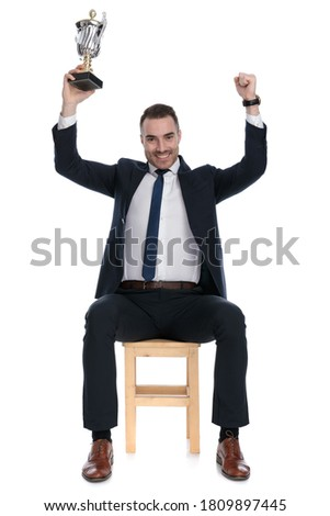 elegant man celebrating with hand in the air while sitting  Stock photo © feedough