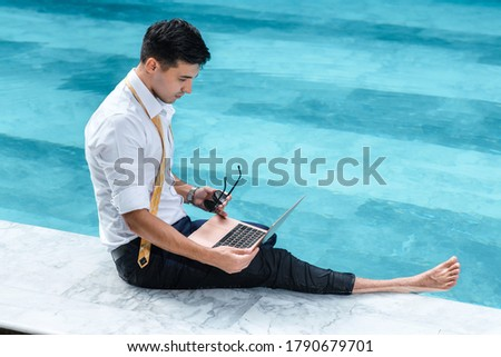 Man sitting at a poolside in front of a laptop computer Stock photo © photography33