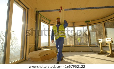 Construction worker carrying a heavy plank Stock photo © photography33