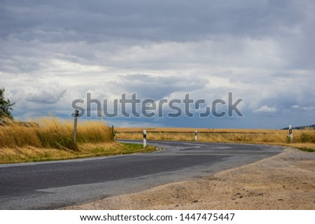 rural road and field of wheat with low dark cloud stock photo © mycola