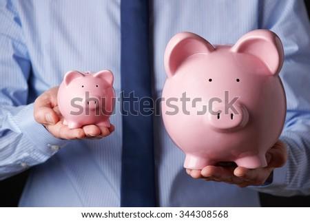 Businessman Holding Large And Small Piggy Bank Stock photo © HighwayStarz