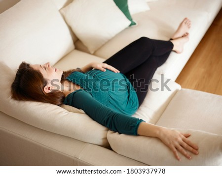 Mid-adult woman expecting baby lying on sofa Stock photo © Lopolo