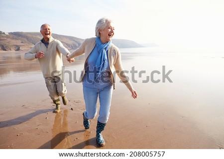 couple running along autumn beach stock photo © dolgachov
