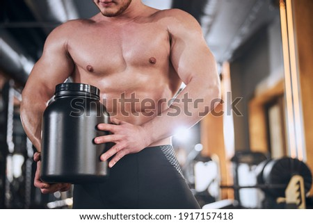 Cropped image of handsome young sportsman holding vitamins Stock photo © deandrobot