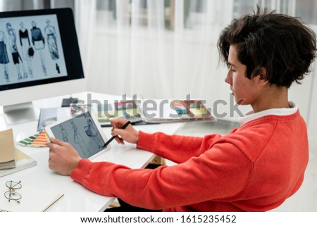 Serious young designer with pen pointing at fashion model on tablet screen Stock photo © pressmaster