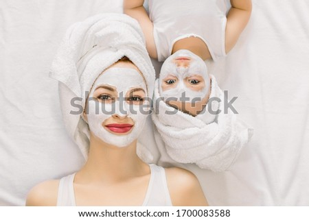 top view of beautiful young mother and her daughter in bed at home foto stock © lopolo