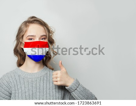 Netherlands COVID-19 Coronavirus concept. Dutch flag on happy Asian doctor medical face mask print f Stock photo © Maridav