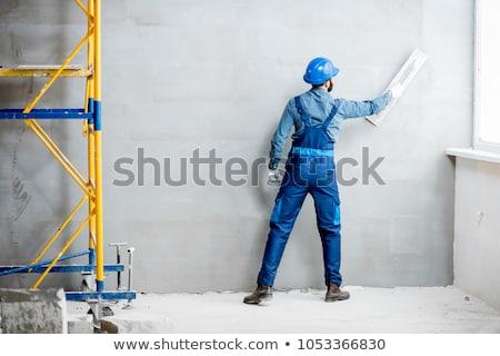 Plaster worker on scaffold working Stock photo © Kzenon