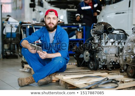 young bearded worker of machine repair service holding touchpad stock photo © pressmaster