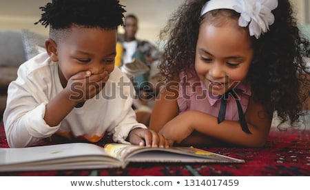 Front view of cute African American sibling lying on floor and reading a storybook in a comfortable  Stock photo © wavebreak_media