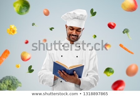 happy indian chef reading cookbook over vegetables Stock photo © dolgachov