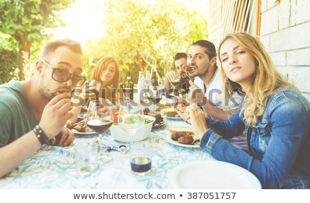 group of young people sitting by the table and drinking red wine stock photo © boggy