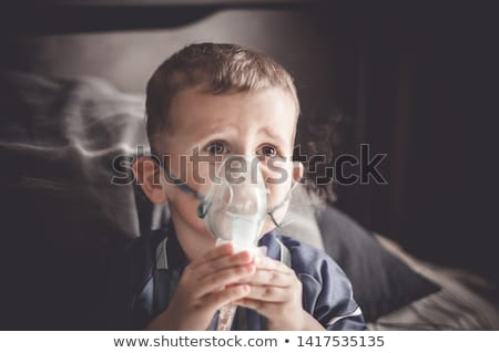 Boy making inhalation with a nebulizer at home Stock photo © galitskaya