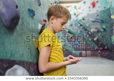 Tired or sad youngster in yellow t-shirt leaning against climbing equipment Stock photo © pressmaster
