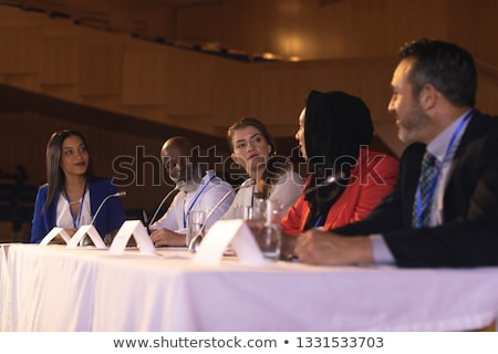 Side view of mixed race business colleague sitting and  discussing with each other in the auditorium Stock photo © wavebreak_media