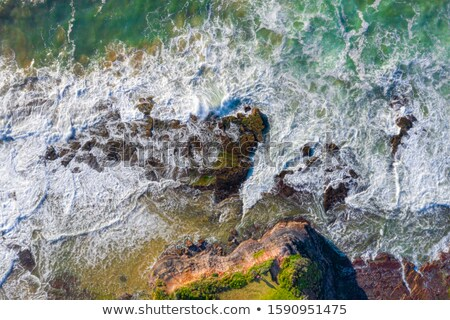 Water flowing over coastal rocks and eroded rock chasms Stock photo © lovleah
