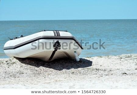Rubber boat on a sand seashore on a blue sky background. Stock photo © artjazz